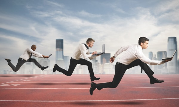 businessmen run on a racetrack while carrying laptops simulating third party logistics competing in the face of shorter contracts
