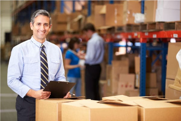 small business manager standing in a warehouse trying to compete with Amazon