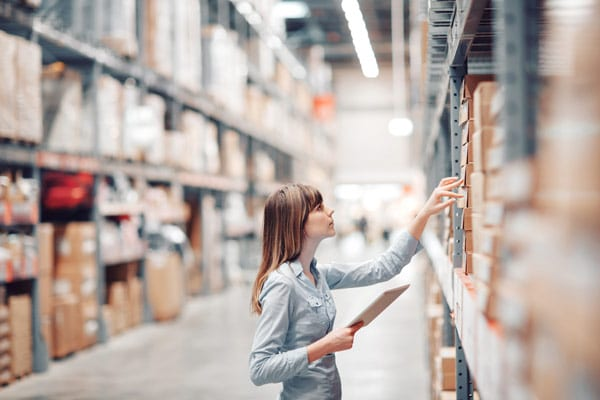 woman with a tablet picking inventory from a warehouse rack
