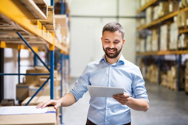 warehouse manager looks at tablet and likes what he sees
