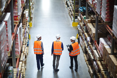 Three warehouse employees adding SKUs to everything for better inventory control